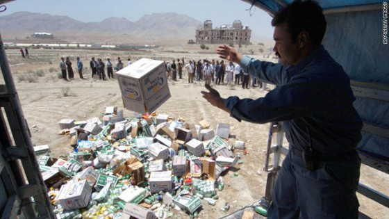 An Afghan policeman throws a box of beer out of a truck to be destroyed in Kabul on July 17 2006 560x315