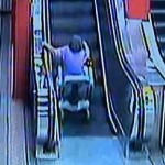 Woman on Motorized Scooter Challenges Escalator, Loses
