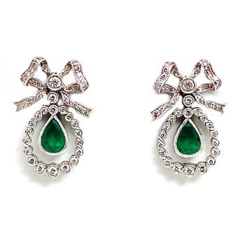 Lady's Victorian style emerald, diamond and white gold earrings, designed in the shape of a bow