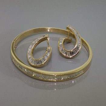 Fashion set: gold bracelet with diamonds and unique earrings with diamonds