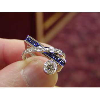 Unique Criss-Cross Band geaturing a round Diamond