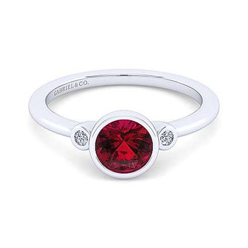 Garnet birthstone ring with two diamond accents